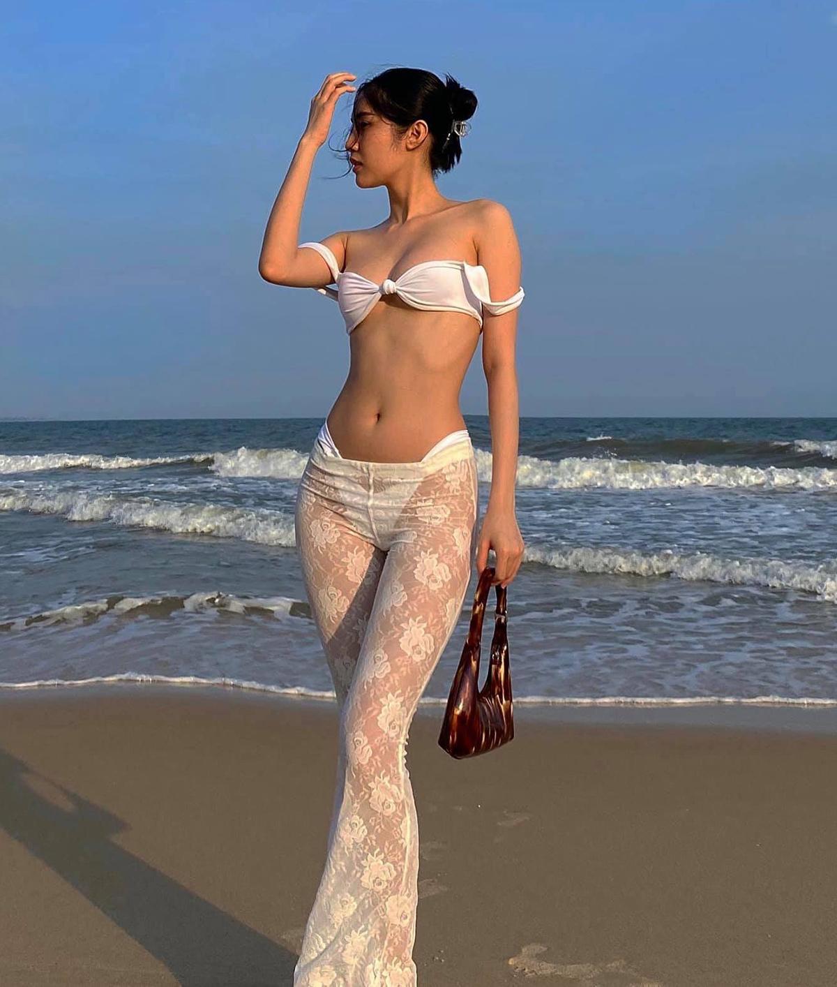 Thay vì mặc bikini như thông thường, chân dài Quỳnh Hương tăng độ quyến rũ cho trang phục trên biển bằng cách mix quần ren mỏng manh phía ngoài.