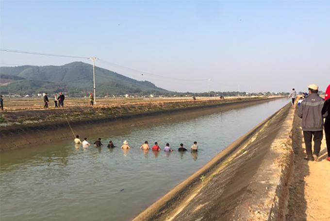 Lực lượng cứu hộ nắm tay nhau lội dọc sông để tìm kiếm nạn nhân. Ảnh: CTV