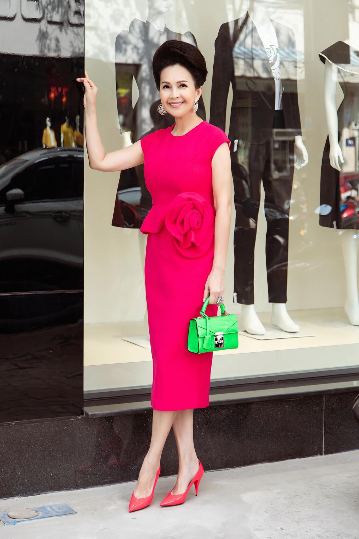 Diễn viên Diễm My xuất hiện nổi bật trong bộ váy phom bodycon với hoạ tiết hoa hồng 3D làm điểm nhấn. Chị chọn túi xách với tông xanh neon nổi bật để phối cùng sắc hồng rực rỡ của chiếc váy.