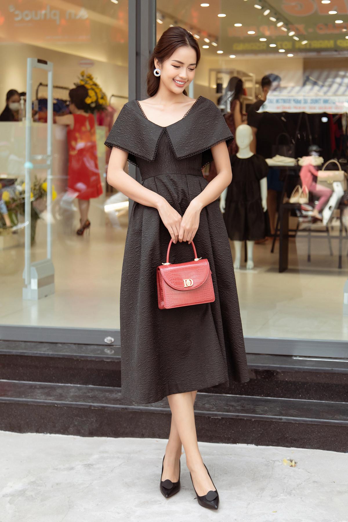 Ngọc Châu bất ngờ đụng hàng Lan Ngọc, nhưng với thiết kế có tông màu đen huyền bí. Người đẹp phối bộ váy cùng chiếc túi đỏ xinh xắn, nổi bật.