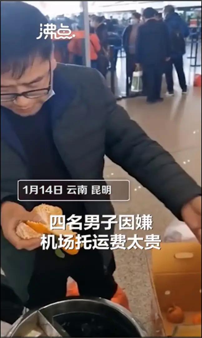 Người đàn ông Trung Quốc ăn cam ở sân bay.