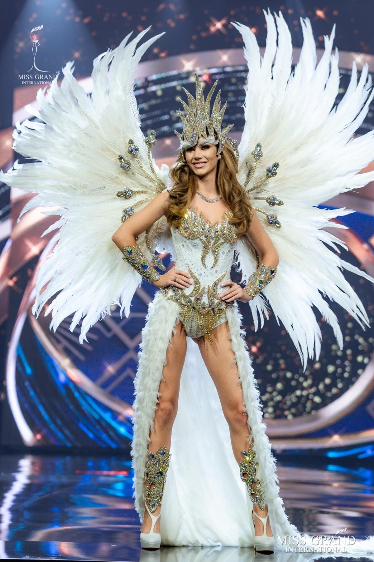 Hơn 60 thí sinh Hoa hậu Hòa bình Quốc tế 2020 thi trang phục dân tộc ở trong một hội trường ở Bangkok, tối 24/3. Các người đẹp trình diễn theo thứ tự alphabet tên quốc gia. Họ có 40 giây catwalk, pose dáng. Những bộ quốc phục với kiểu dáng sexy, độc đáo được ưa chuộng. Trong hình là trang phục dân tộc của thí sinh Argentina.