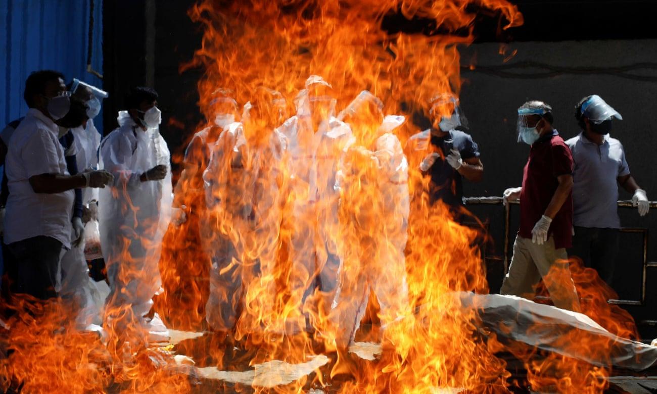 Người thân mặc đồ bảo hộ tham gia lễ hỏa táng bệnh nhân Covid-19 tại New Delhi. Ảnh: Reuters.