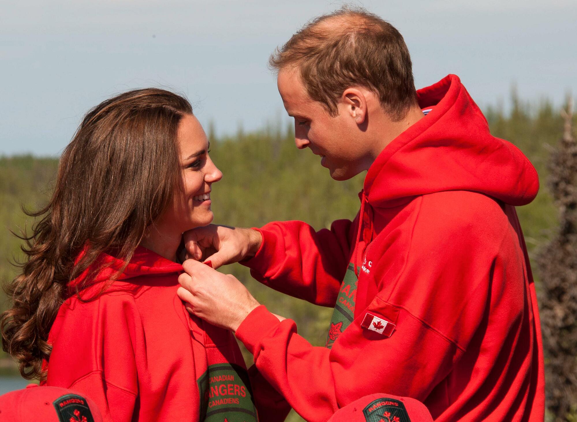 William giúp Kate mặc chiếc áo hoodie đỏ khi cả hai trở thành thành viên danh dự của Đội Kiểm lâm Canada.