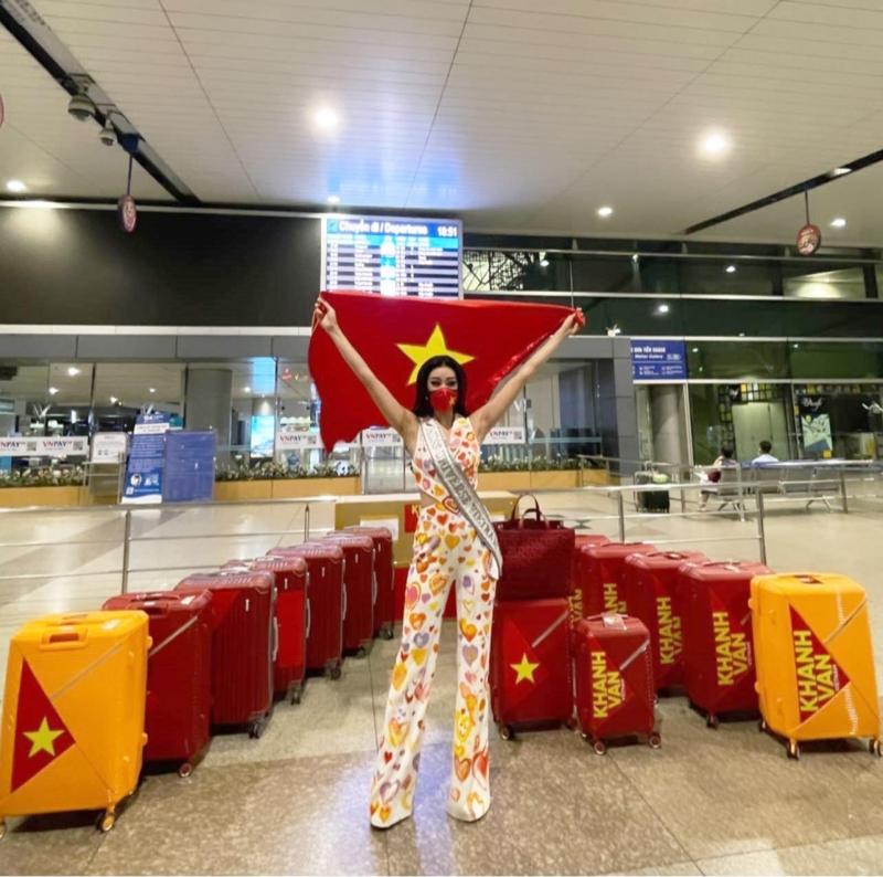 Khánh Vân giơ cao lá cờ Tổ quốc ở sân bay.