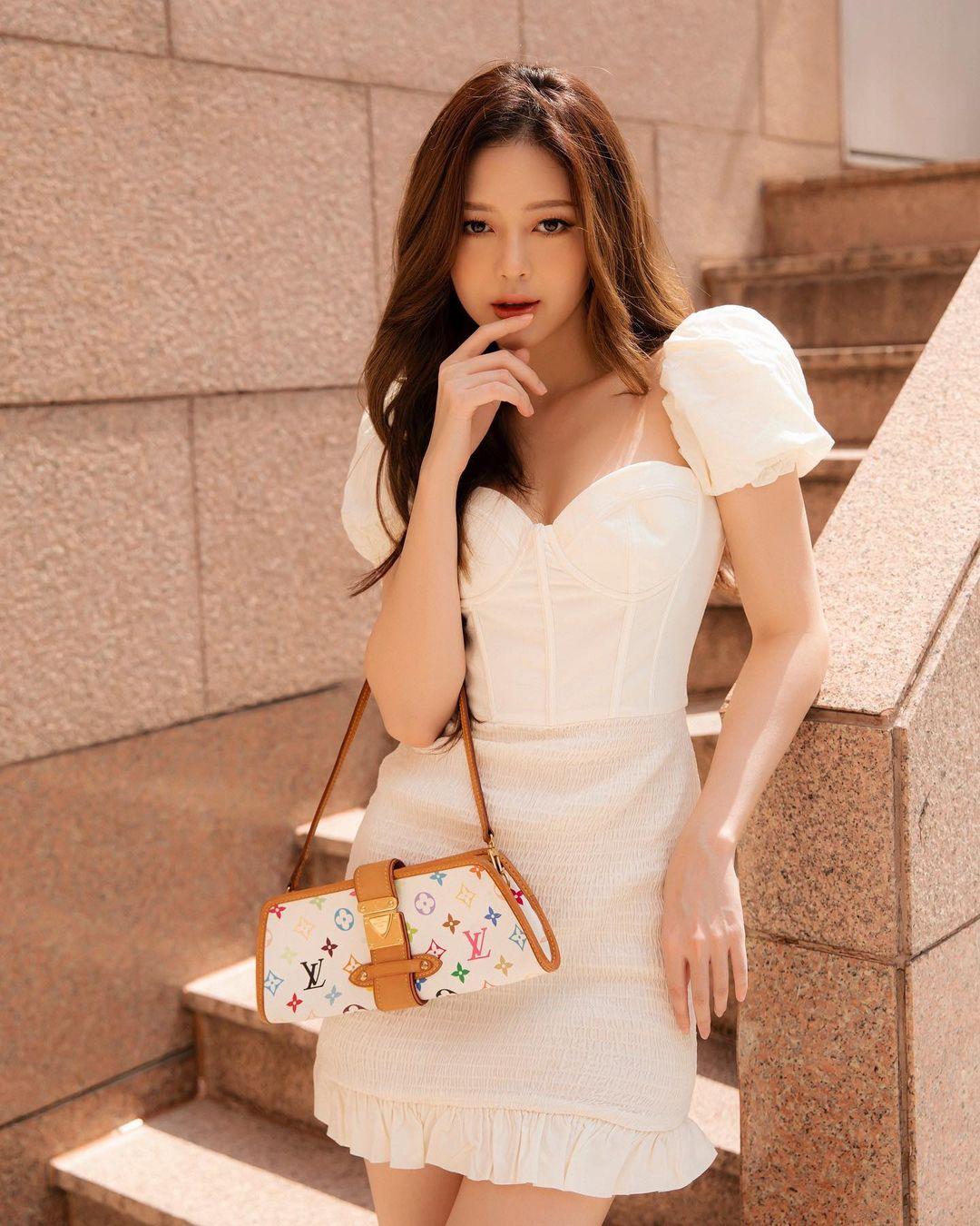 Diện váy trắng tay bồng ngọt ngào, Liz Kim Cương dùng chiếc túi vintage của Louis Vuitton làm điểm nhấn.