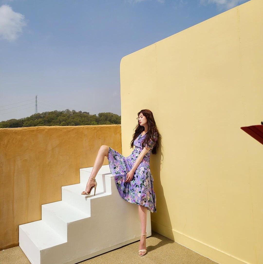 Nana diện váy hoa tím mộng mơ với kiểu tạo dáng khoe chân là chủ yếu.