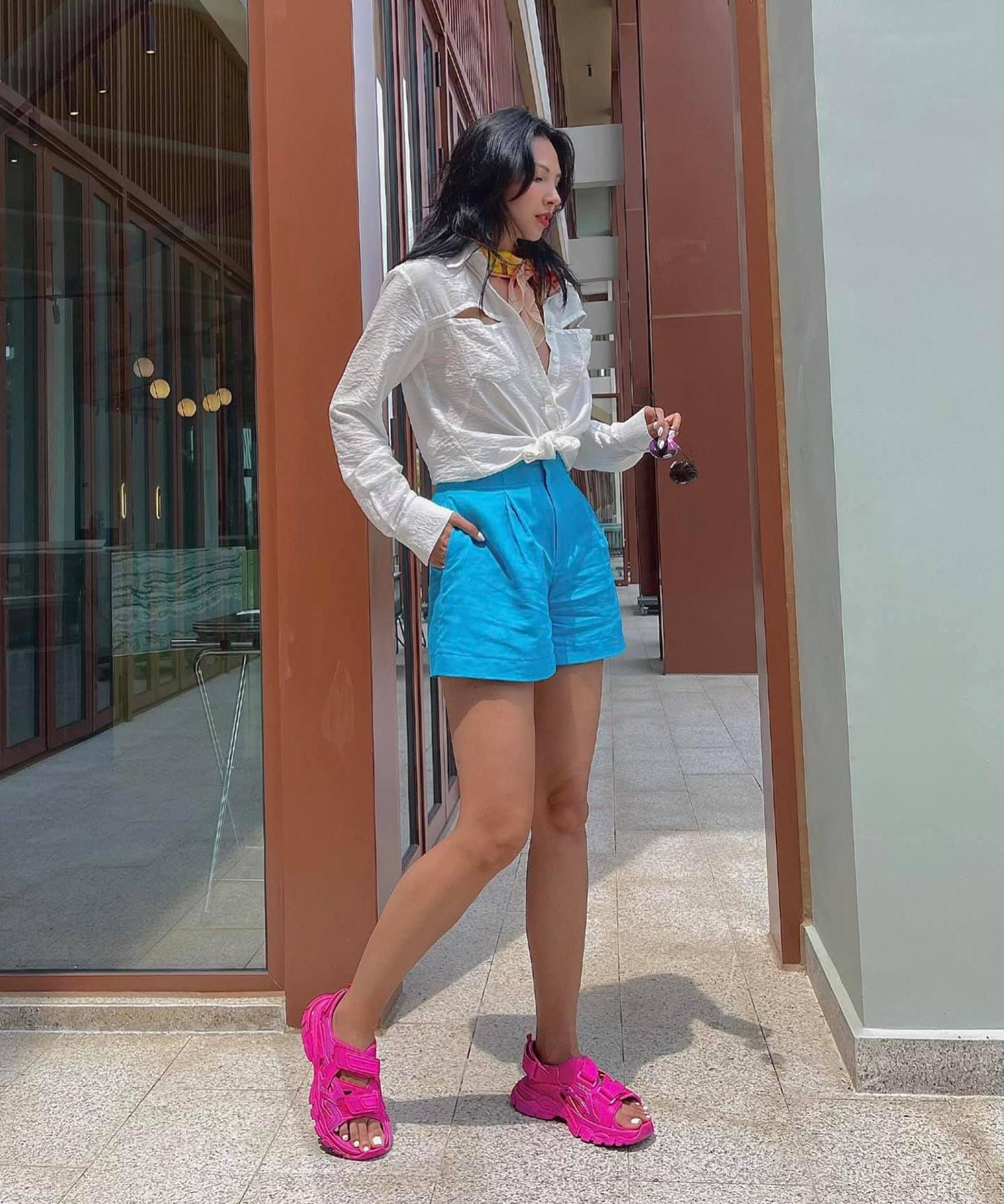 Minh Triệu khoe style mùa hè nổi bần bật với nhiều items tông neon. Chân dài không ngại kết hợp quần xanh cùng dép hồng dù đây không phải là hai gam màu hợp cạ.