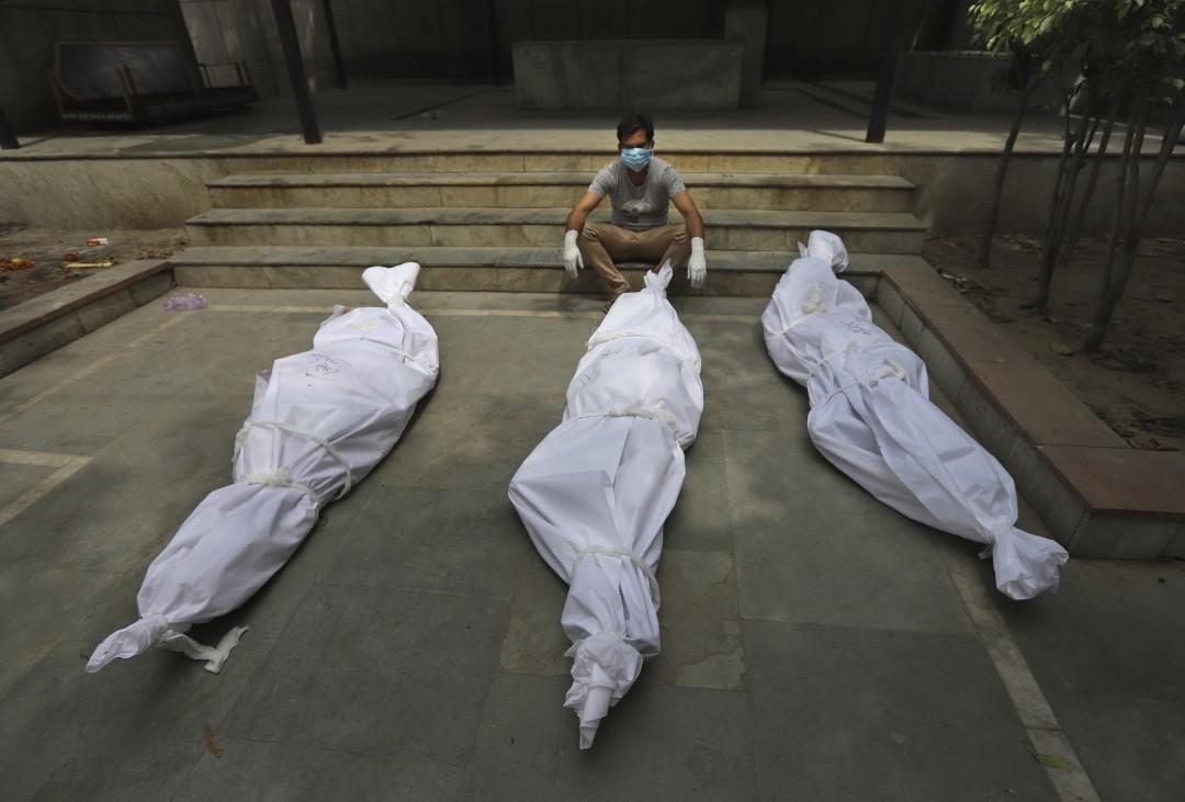 Một người đàn ông chờ hỏa táng người thân, đặt gần hai thi thể khác, ở New Delhi. Ảnh: AP.