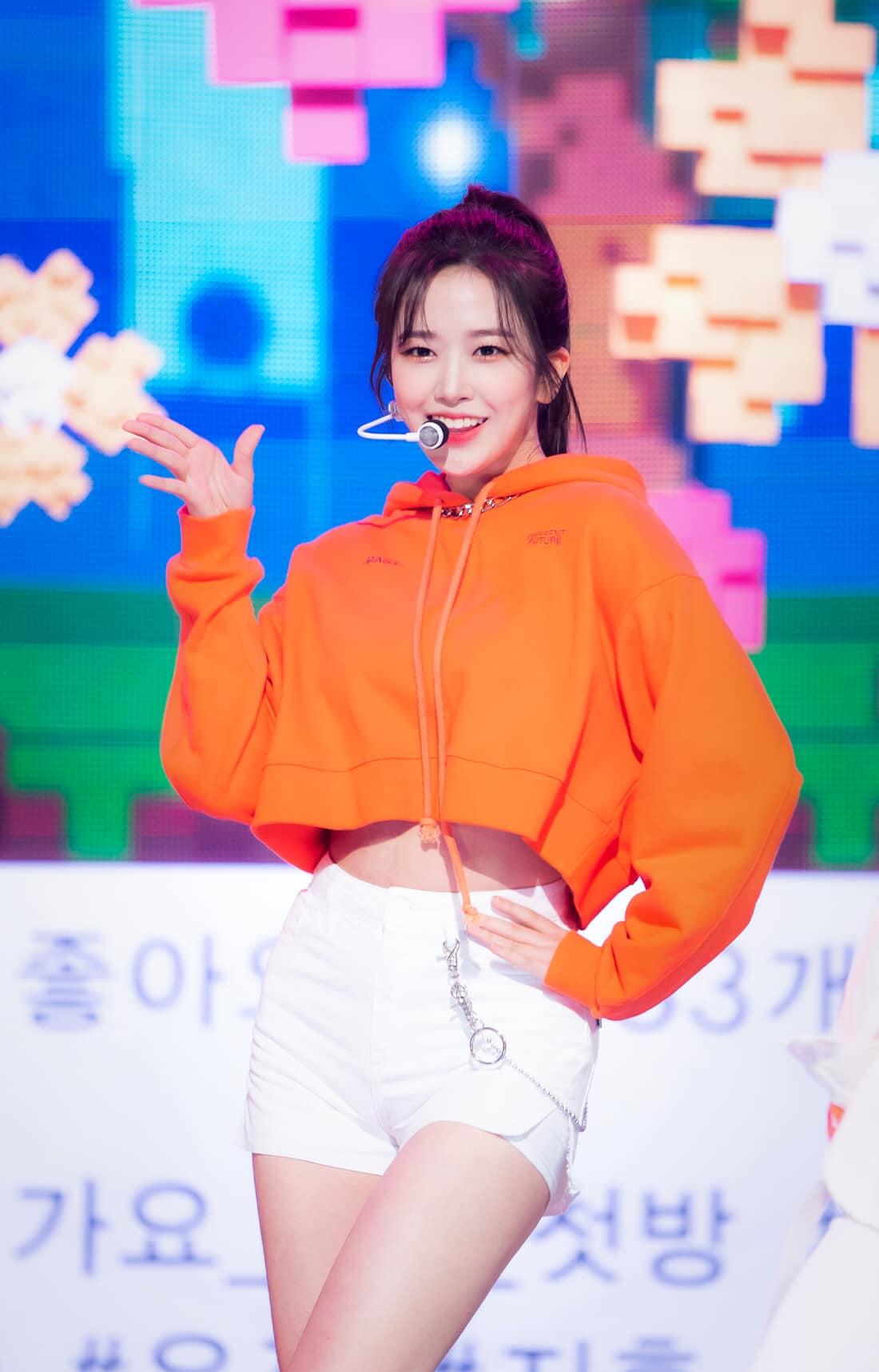 Trong một sân khấu của các MC, Ahn Yu Jin mặc áo hoodie crop top và quần shorts khoe dáng đẹp. Llàn da trắng mịn và gương mặt rạng rỡ của mỹ nhân IZONE rất hợp với tông màu cam - trắng.
