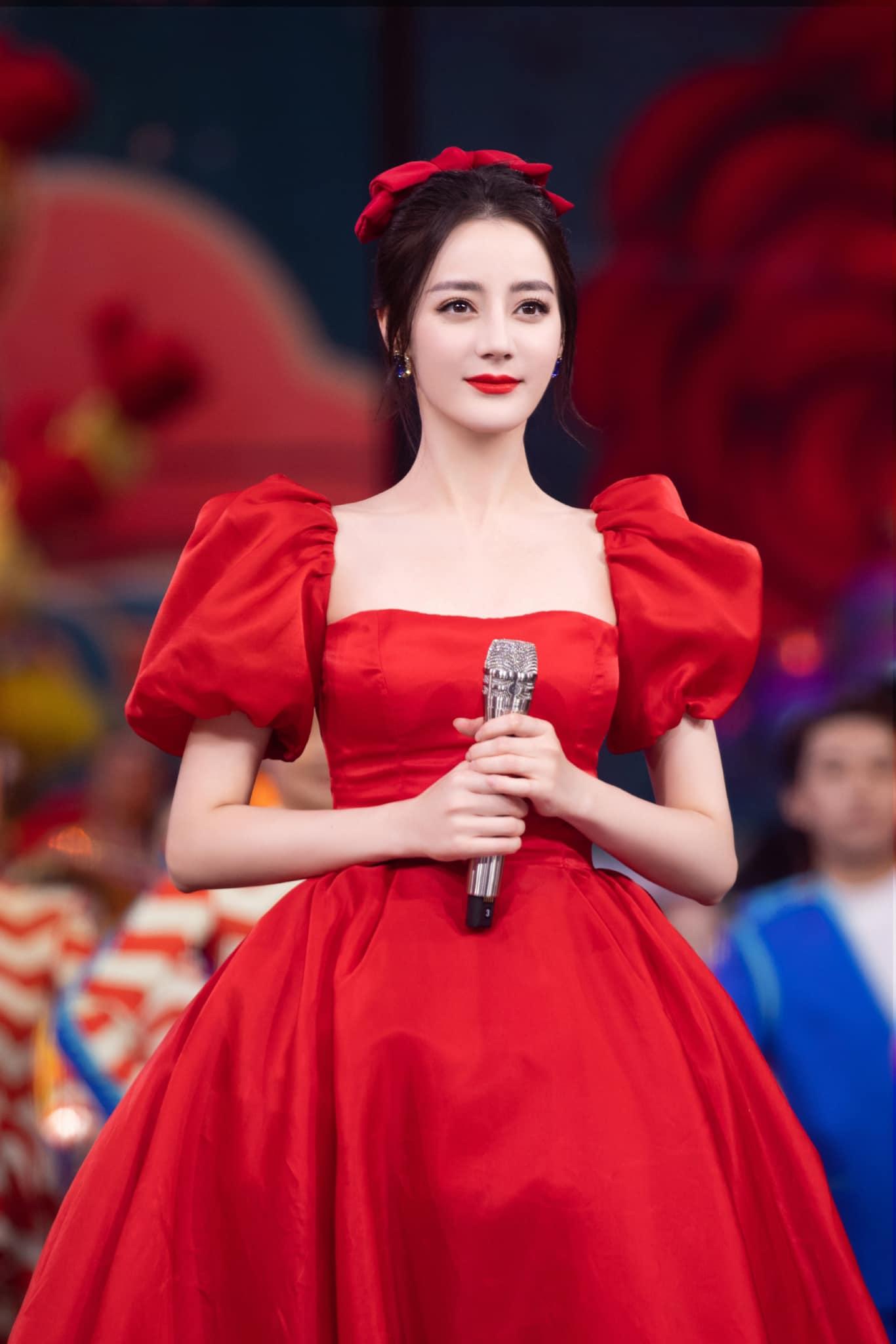Chiếc váy cổ vuông tay bồng siết chặt vòng eo đi kèm nơ cài <a href='https://www.thegioitoc.top' target='_blank'>tóc</a> giúp Địch Lệ Nhiệt Ba tôn lên làn da trắng như tuyết, đôi môi đỏ son kiêu kỳ.