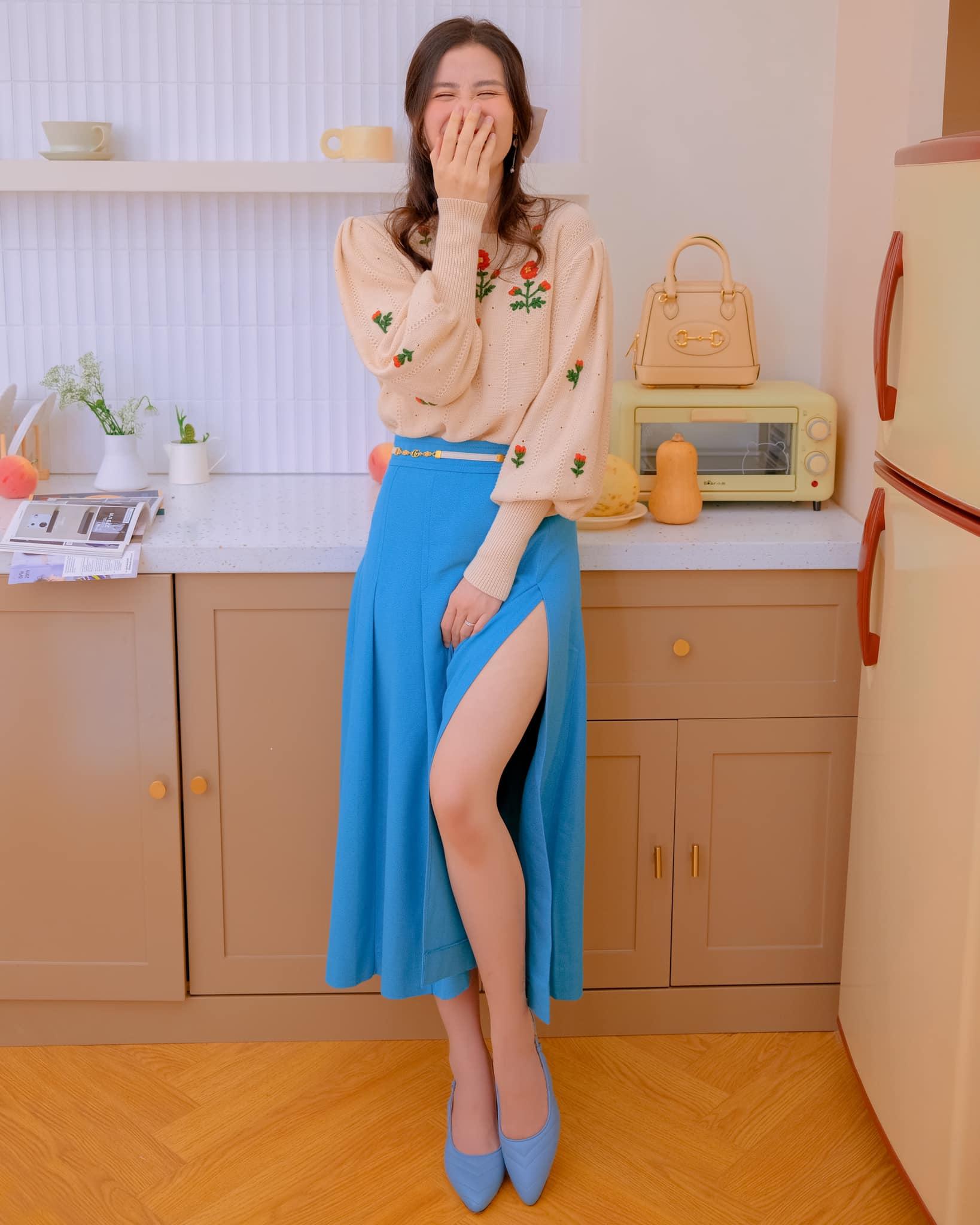 Đông Nhi được khen trẻ xinh như teen girl khi phối áo len thêu hoa cùng chân váy xanh xẻ tà. Bà mẹ một con còn khéo hack tuổi bằng kiểu tóc kẹp nửa dễ thương.
