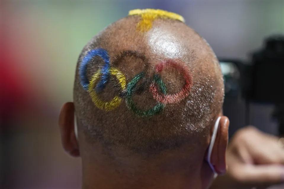 Huấn luyện viên người Mông Cổ, Undralbat Lkhagva cắt và nhuộm 5 vòng tròn Olympic lên <a href='https://www.thegioitoc.top' target='_blank'>tóc</a> khi ông theo dõi nội dung 10m bắn súng hơi nữ tại Trường bắn Asaka, ngày 25/7. Ảnh: Alex Brandon/AP