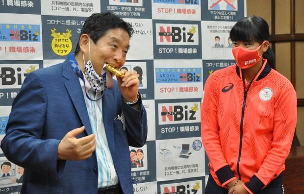 Ông Takashi Kawamura bị chỉ trích vì cắn huy chương Olympic của VĐV Miu Goto. Ảnh:Mainichi