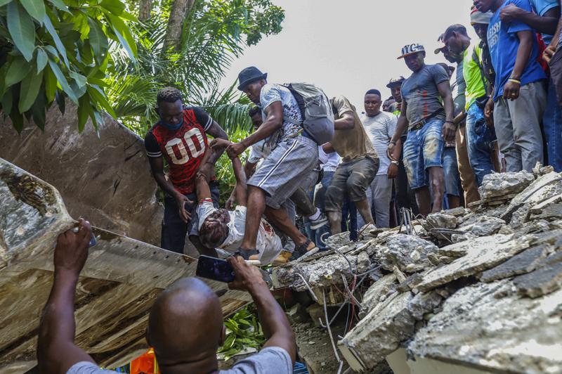 Người dân đưa thi thể của Gabriel Fortune, chính trị gia lâu năm và là cựu thị trưởng của Les Cayes, từ đống đổ nát của khách sạn Le Manguier bị phá hủy bởi trận động đất ở Les Cayes, Haiti. Ảnh: AP
