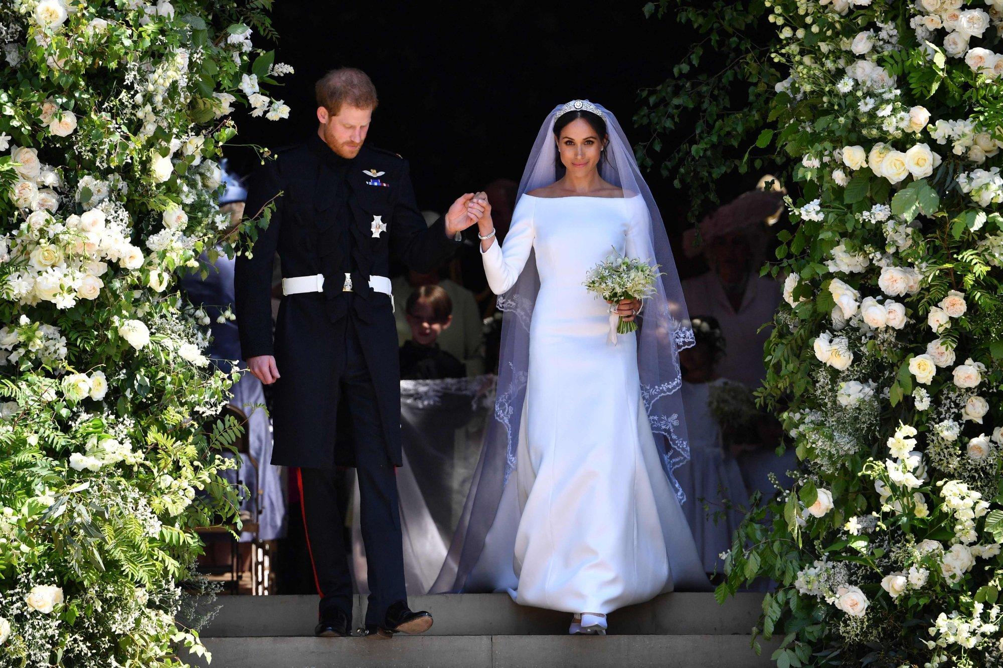 Meghan Markle được Hoàng tử Harry đỡ khi bước xuống bậc thang, nhưng sự thật là cô ấy không được phép cúi xuống. Ảnh: AFP