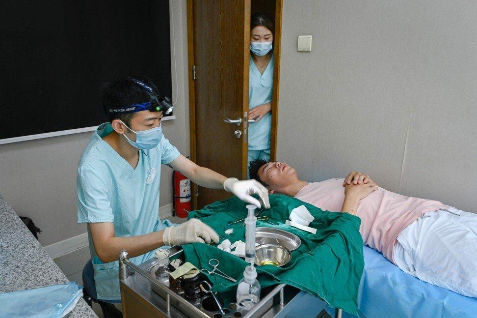Ngày 22/7, Xia Shurong (phải) trên bàn phẫu thuật thực hiện thủ thuật thẩm mỹ. Ảnh: AFP