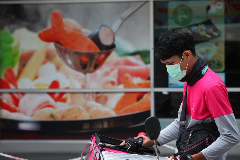Một nhân viên giao đồ ăn mặc đồng phục hãng Foodpanda tại Thái Lan. Ảnh:Bangkok Post