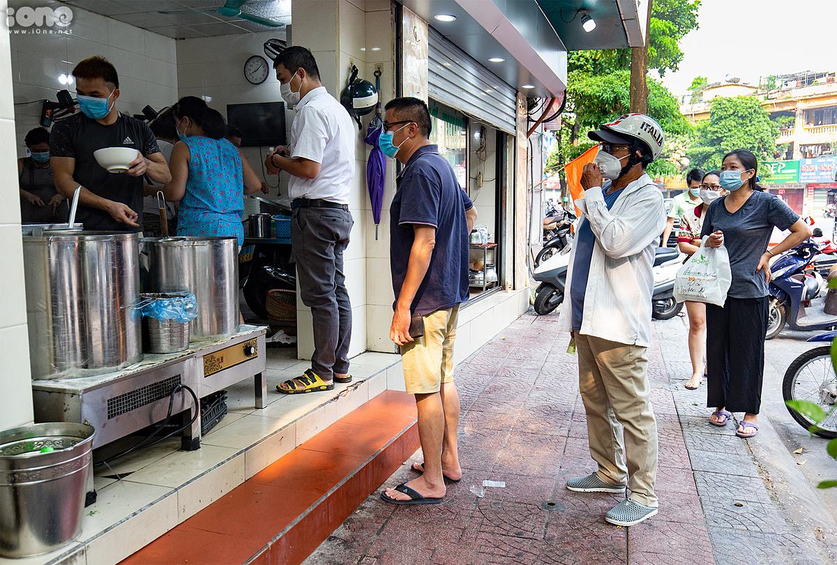 Người dân sinh sống ở vùng xanh xếp hàng chờ mua phở, xôi sáng 13/9, sau khi UBND quận Long Biên cho phép hàng quán mở cửa đón khách trở lại. Ảnh: Tùng Đinh