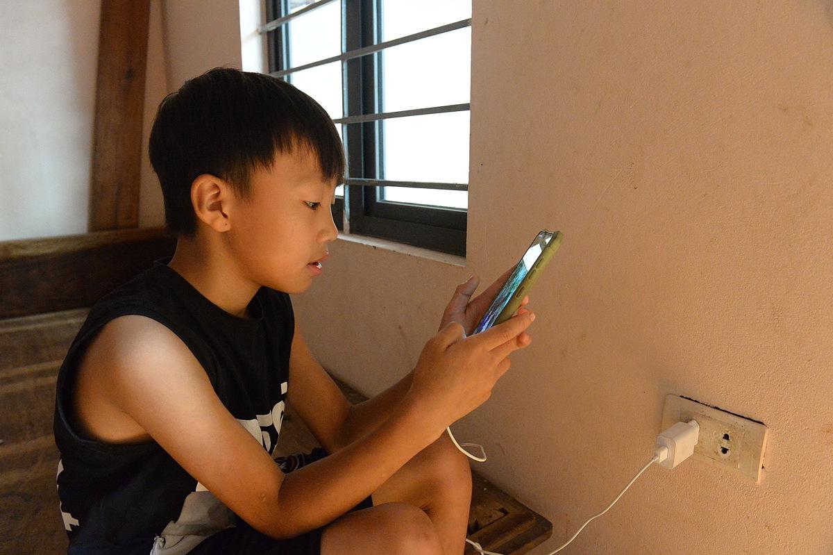 Cậu con trai học lớp 3 tranh thủ dùng điện thoại khi các chị nghỉ giải lao.