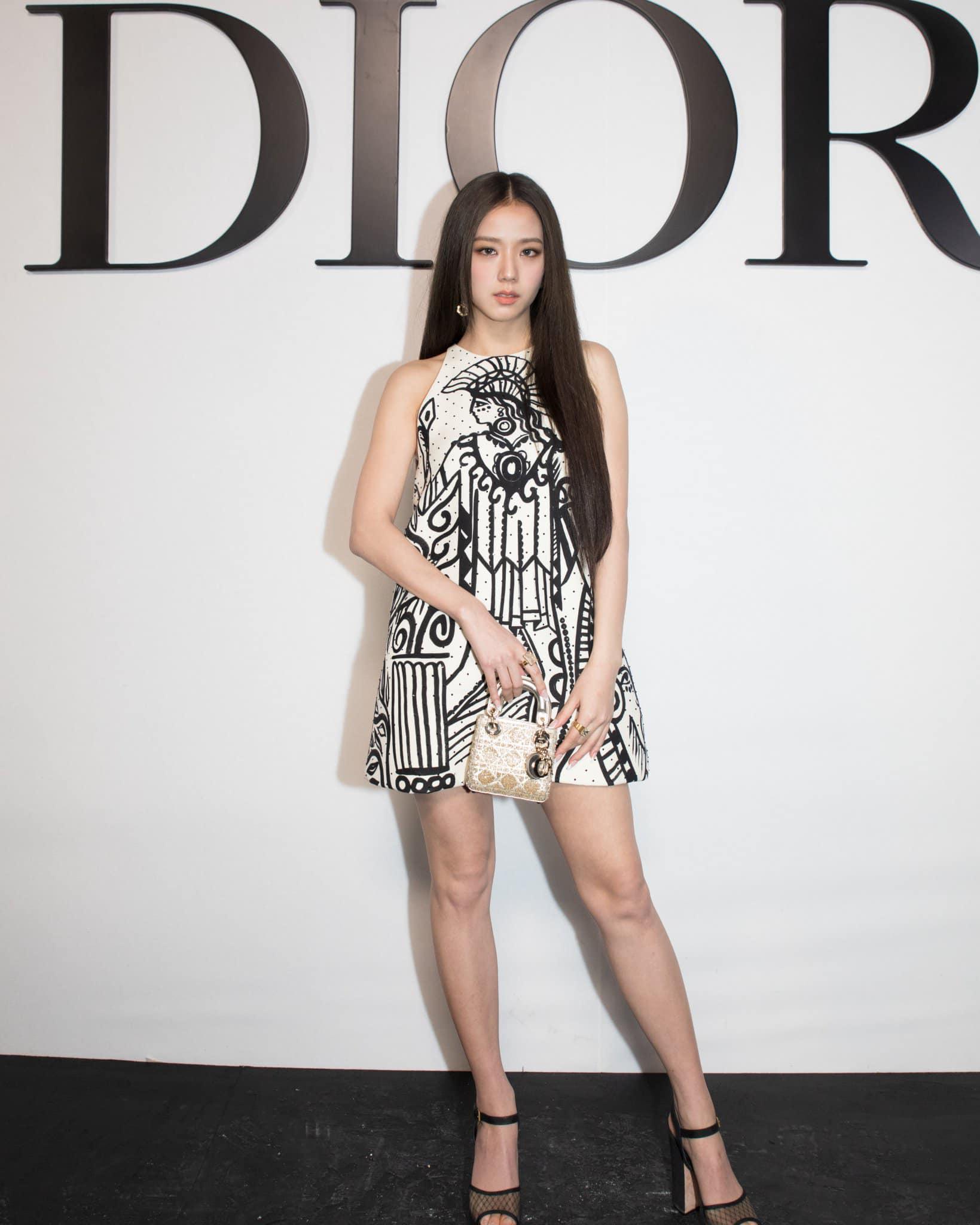 Bộ váy không tay dáng suông mà Ji Soo mặc nằm trong BST mới nhất của Dior với họa tiết Hy Lạp cổ màu đen nổi bật trên nền trắng. Đi kèm trang phục, nữ idol xách túi Lady Dior phiên bản mini cùng giày cao gót tôn chiều cao.